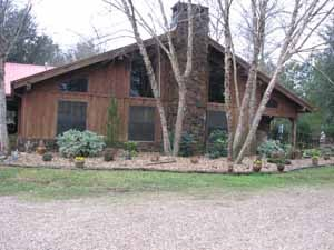 1.5 hrs from the Gulf Coast; Rustic Lodge style home w/large horse barn/shop/covered round pen